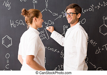 Man and woman wearing labcoats standing in front of a blackboard