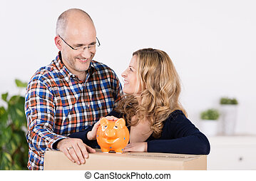 Man and woman with a carton and piggy bank