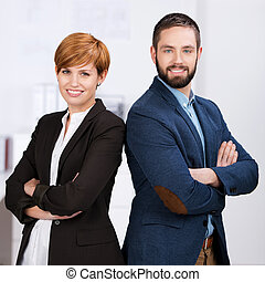 Portrait of happy confident businessman and businesswoman with arms crossed standing in office