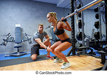man and woman with bar flexing muscles in gym - sport, ...