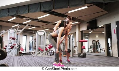 man and woman with barbell flexing muscles in gym