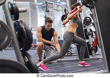 man and woman with barbell flexing muscles in gym - sport, ...