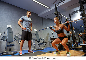 man and woman with barl flexing muscles in gym - sport, ...