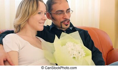 man and woman with bunch of flowers sitting on divan
