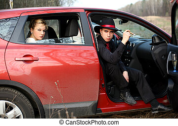 man and woman with cigar, wine in car