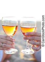 Man and woman with glass of rose wine on beach picnic