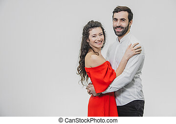 Man and woman with long hair. The wife hugged her husband. Back view. Valentine's Day. I Woman dressed in red man dress in white shirt.