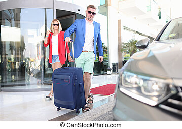 Man and woman with luggage leaving hotel by car