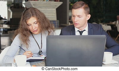 Man and woman with modern laptop work in cafe