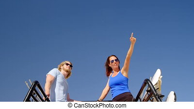 Man and woman with sand boards looking at a distance 4k