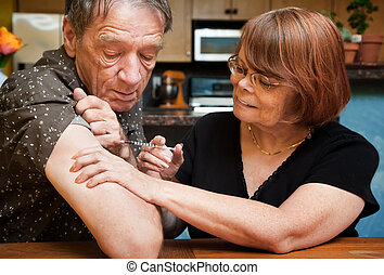 Man and woman with small hypodermic needle - Senior woman...