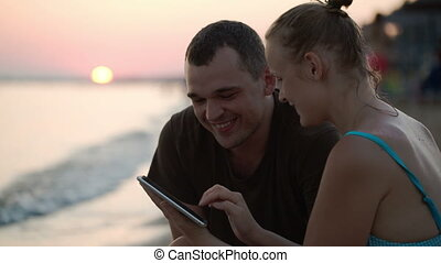Man and woman with tablet PC on the beach