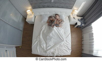 Man and woman with tattoos sleeping in bed