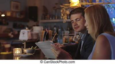 Man and woman with touch pad in the bar