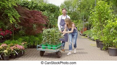 Man and woman with wagon in garden - Horizontal outdoors...