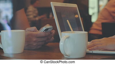 Man and woman work in cafe using gadgets