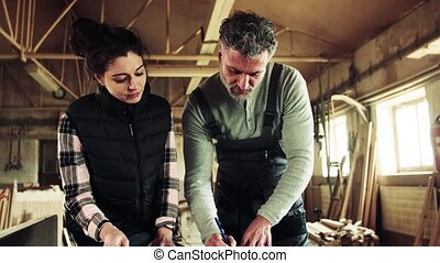 Man and woman workers in the carpentry workshop. - Portrait...