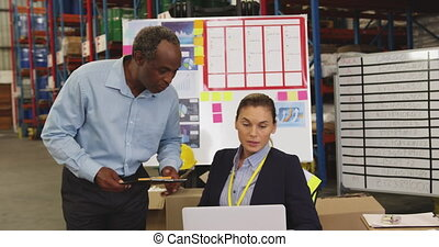 Man and woman working at a desk in a warehouse 4k