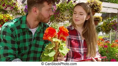 Man and woman working in blooming garden - Young girl using...