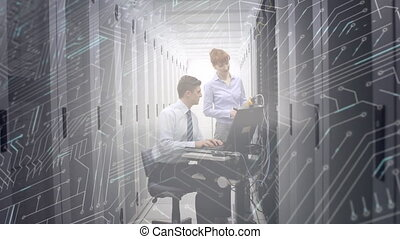 Man and woman working in computer server room while a glowing circuit board moves in foreground