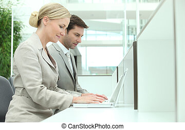 man and woman working on computers