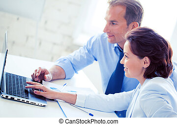 man and woman working with laptop in office