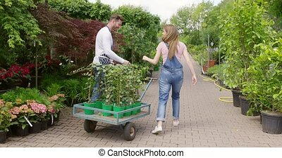 Man and woman working with plants - Side view of man in...