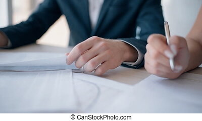 Man and woman working with startup project, sitting at table in office interior.