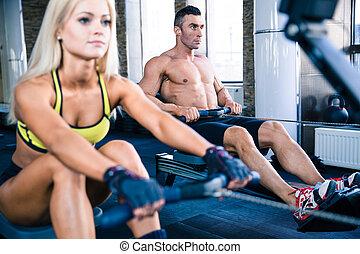 Man and woman workout on training simulator - Muscular man ...