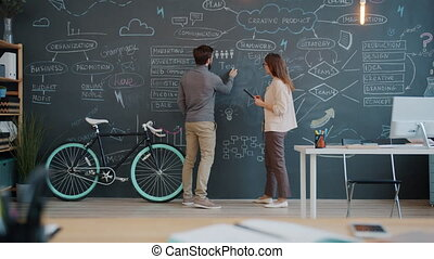 Man and woman writing on chalk board discussing business ...