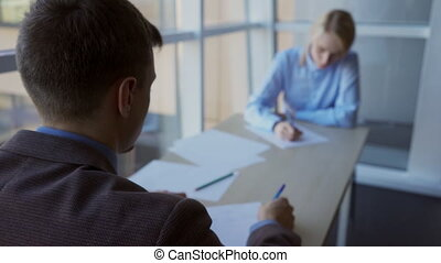Man and woman writing while sitting at table in comfortable office.