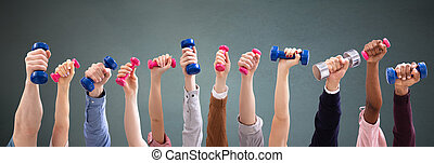 Man And Woman's Hand Holding Dumbbells In Green Backdrop