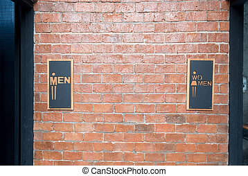 Man and women signs on public restroom on brick wall