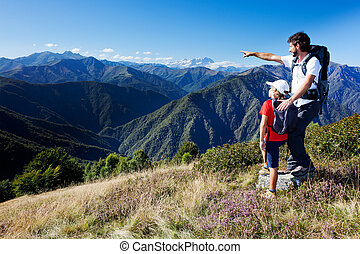 Man and young boy standing in a mountain meadow. The man...
