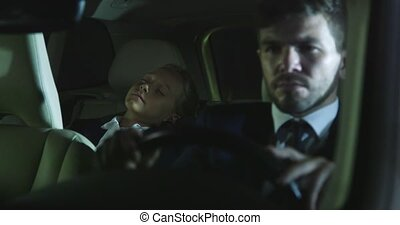 Man and young girl drive in car at night.