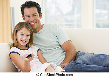 Man and young girl in living room with remote control...
