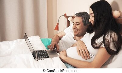 Man and young pregnant woman shopping online using their laptop in bed