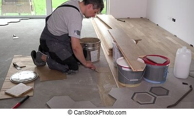 Man apply glue adhesive on floor for parquet board laying....