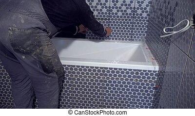man apply tiles on bathtub side in bathroom. Static closeup...