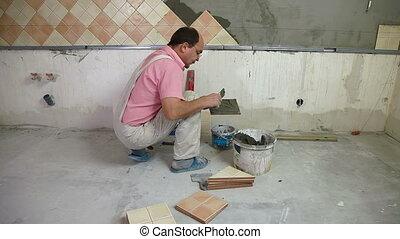 putting mortar on Tiles - man applying ceramic tile to a...