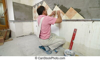 Man applying ceramic tile to a Kitchen wall, Side View, Wide...