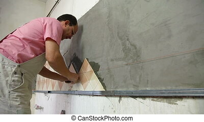 Man applying ceramic tile to a Kitchen wall