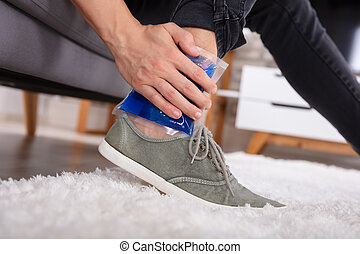 Man Applying Ice Gel Pack On An Ankle