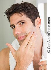 Man applying moisturizer on face - Close up portrait of a...