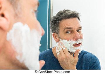 Man Looking In Mirror Applying Shaving Cream