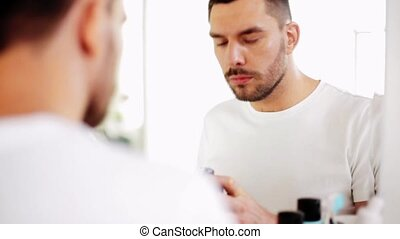 man applying shaving foam to beard at bathroom