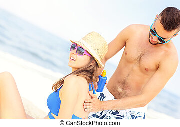 Man applying sunscreen on the back of his woman