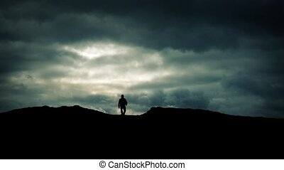 Man Approaches Over Hill On Dramatic Sky Silhouette