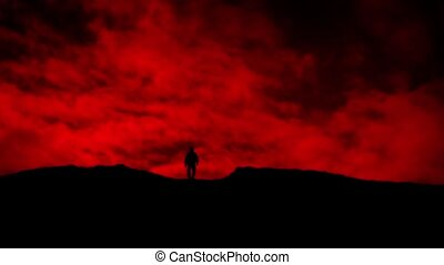 Man Approaches Over Hill On Red Sky Silhouette