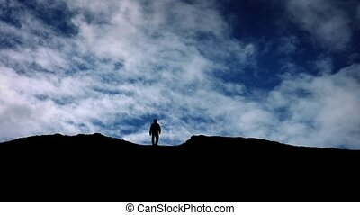 Man Approaches Over Hill Top Silhouette